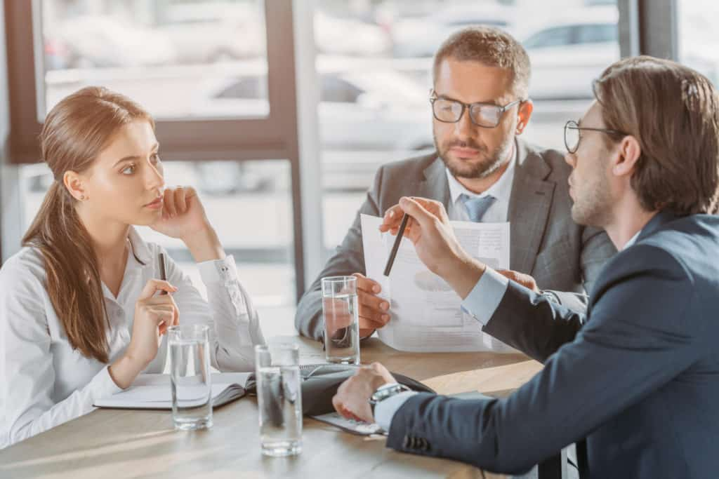 group of business people with contracts having meeting at modern office